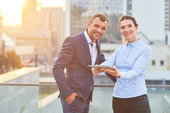 Business couple with tablet smiling. Happy caucasian men and woman. Make profit using social media Stock Images