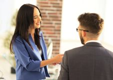 Smiling businesswoman communicating with male colleague. Business couple talking in office Royalty Free Stock Photos