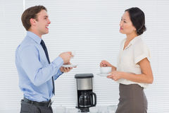 Business couple with tea cups chatting in office Royalty Free Stock Images