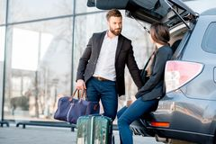 Business couple traveling by car. Business couple sitting in the car trunk with suitcase in the city. Business traveling by car concept royalty free stock photos
