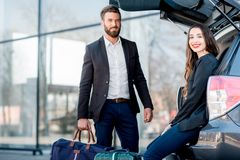 Business couple traveling by car. Business couple sitting in the car trunk with suitcase in the city. Business traveling by car concept stock images