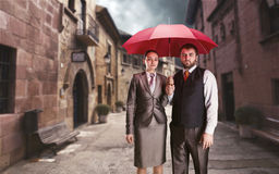 Business couple under umbrella Stock Photos