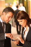 Business Couple Using Cellphone Stock Image