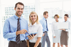 Business couple using digital tablet with colleagues behind Stock Image