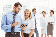 Business couple using digital tablet with colleagues behind Royalty Free Stock Photo