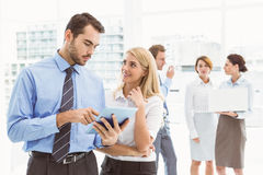 Business couple using digital tablet with colleagues behind Stock Photography