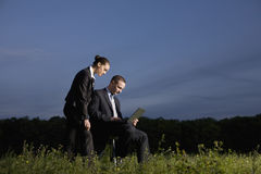 Business Couple Using Laptop In Field Stock Images