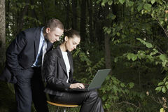 Business Couple Using Laptop In Forest Stock Photography