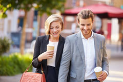 Business Couple Walking Through Park With Takeaway Coffee. Happy Business Couple Walking Through Park With Takeaway Coffee Wearing Smart Clothing royalty free stock image