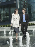 Business Couple Walking Between Water Jets Of Fountain Stock Images