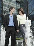Business Couple Walking Between Water Jets Of Fountain Stock Photo