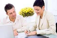 Business couple working. At office, smiling Royalty Free Stock Photography