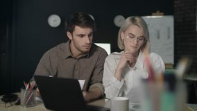 Business couple working on financial project in dark office together. stock footage