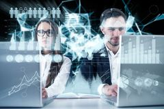 Business couple working, infographics. Young business couple working at their laptops. Graphs and infographics. Double exposure toned image Elements of this Stock Photography