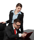 Business Couple. Young business couple looking together to a notebook, isolated against a white background. Selective focus on the man Stock Image