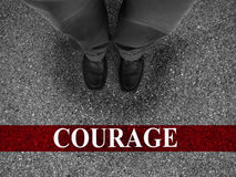 Business Courage. Businessman standing on asphalt starting line with motivation word of courage royalty free stock photo