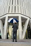 Business Cover. Businessman with umbrella open about to enter a skyscraper for his next appointment royalty free stock photos