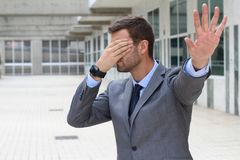 Business covering his eyes to avoid reality stock image