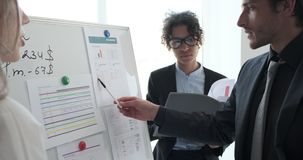Business coworkers discussing with reports on whiteboard at office. Business coworkers discussing with financial reports on whiteboard at office meeting stock footage