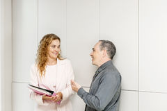 Business coworkers talking in hallway. Man and women discussing work in business office hallway stock images
