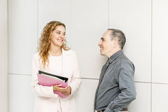 Business coworkers talking in hallway. Man and women discussing work in business office hallway stock image