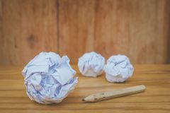 Used pencil with many white crumpled paper ball put on wooden floor. Business Creative and Idea Concept Used pencil with many white crumpled paper ball put on Royalty Free Stock Images