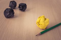 Business Creative and Idea Concept : Used pencil with yellow crumpled paper ball put on wooden floor and black crumpled paper ball. In the background. Selective Royalty Free Stock Images