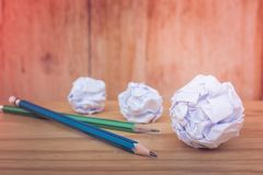 Business Creative and Idea Concept : Used pencils with many white crumpled paper ball put on wooden floor in vintage style. stock photo