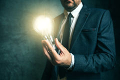 Business creativity concept with businessman holding light in ha Royalty Free Stock Photo