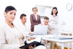 Business crew. Businesswoman sitting in front, writing notes, looking at camera, smiling. Four business colleagues working on laptop computer in background royalty free stock images