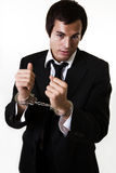 Business crime. Professional young business man in business suit with hands in handcuffs showing white collared crime Stock Photo