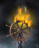 Business Crisis. And financial disaster economic symbol with a burning navigation wood marine ship wheel in flames representing danger and need for insurance on Royalty Free Stock Images