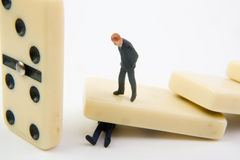 Business Crisis. Miniature man standing on domino that is on top of another miniature Stock Images