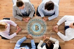 Business team at table with bitcoin icon Stock Photo