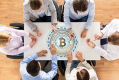 Business team at table with bitcoin icon Stock Photos