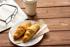 Business cup of coffee with croisant and newspaper on desk Stock Photo