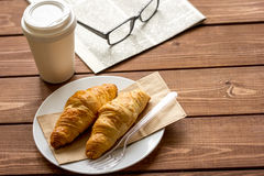 Business cup of coffee with croisant and newspaper on desk Stock Photography