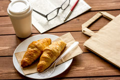 Business cup of coffee with croisant and newspaper on desk Stock Photos