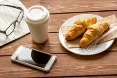 Business cup of coffee with croisant and phone on desk Stock Images