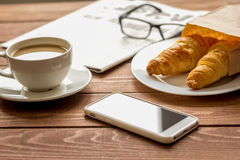 Business cup of coffee with croisant and phone on desk Stock Photos