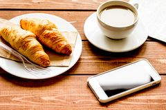Business cup of coffee with croisant and phone on desk royalty free stock photo