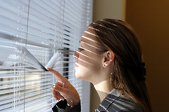 Business curiosity. Woman looking from window through blinds Stock Photo