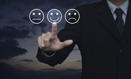 Business customer service evaluation and feedback rating concept. Businessman pressing excellent smiley face rating icon over sunset sky, Business customer royalty free stock photos