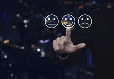 Business customer service evaluation and feedback rating concept. Businessman pressing excellent smiley face rating icon over blur colorful night light city stock images