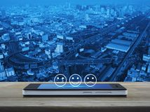 Business customer service evaluation and feedback rating concept. Excellent smiley face rating icon on modern smart mobile phone screen on wooden table over city stock image