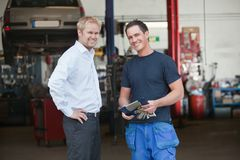 Business Customer Standing With Mechanic. Portrait of a male customer standing with mechanic outside the garage Royalty Free Stock Images