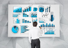 Business data analysis. Young businessman drawing many different blue graphs on a white poster. Back view. Grey geometric background. Concept of presenting data Royalty Free Stock Photos