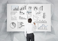 Business data analysis. Young businessman drawing many different graphs on a white poster. Back view. Grey geometric background. Concept of presenting data in Stock Images