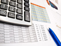 Business data and calculator. Electronic calculator and pen on printed sheets of business data and chart Royalty Free Stock Photos