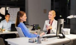 Businesswomen drinking coffee at night office stock image